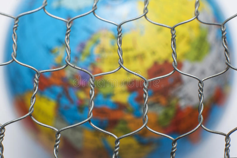 Global map behind a wire fence. The global map behind a wire fence stock photography