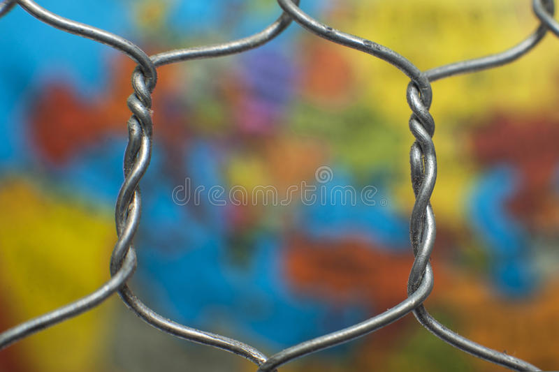 Global map behind a wire fence. The global map behind a wire fence royalty free stock photos