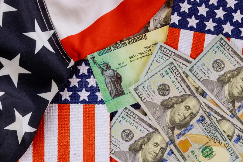 Federal monetary assistance stimulus U.S. economic tax return check USA dollar cash banknote on American flag Global pandemic. Global pandemic Covid 19 lockdown royalty free stock photos