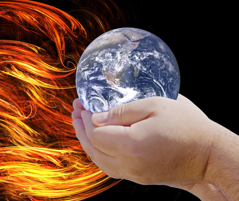 Global Warming. The concept of this image is Global Warming as two hands cradle the World which is close to the fiery heat of abstract flames royalty free stock images