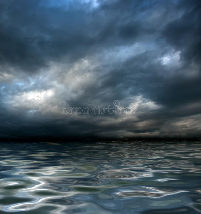 Global warming. Dark cloudy stormy sky with clouds and waves in the sea - global warming concept royalty free stock photos