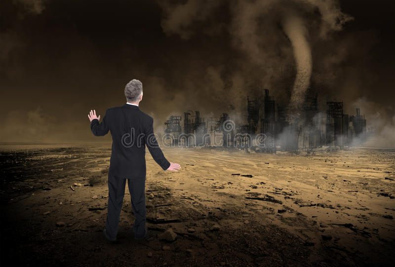 Global Warming, Climate Change, Apocalypse. A businessman stands in a desolate desert and watches a tornado storm destroy a big urban city as global warming and royalty free stock photos