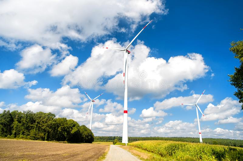 Global warming, climate change. Turbines on field on cloudy blue sky. Alternative energy source. Wind farm in Lower Saxony, Germany. Eco power, green royalty free stock photos