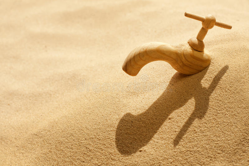 Global warming concept. Global warming climate change faucet in the sand concept stock image