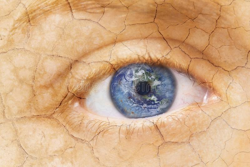 Global warming concept. Close up image of woman cracked textured face with iris earth. Creative composite of macro Eye stock photography