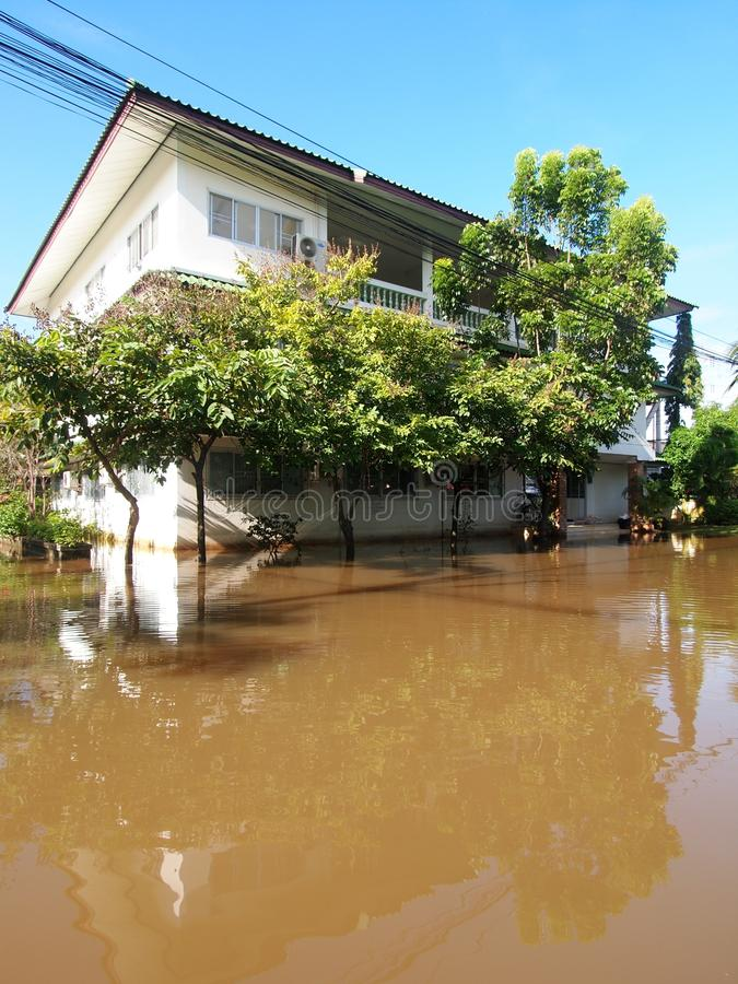Global warming effect in town, low level flood water in urban zone. Authentic picture shows brown dirty water in abandoned village under frequently repeated royalty free stock images
