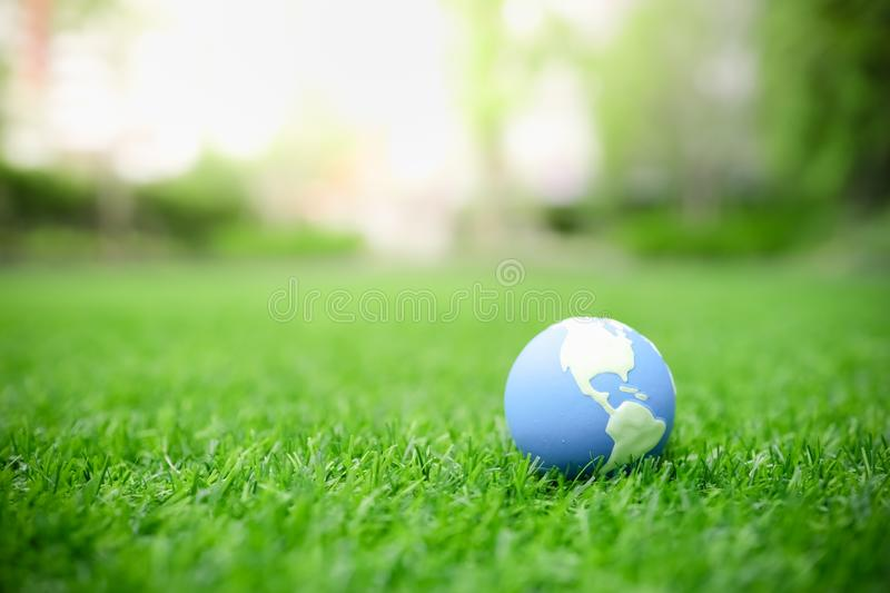 Global Warming, Environment and Ecology Concept. Close up of mini world ball on green grass lawn with rain drop.  royalty free stock images