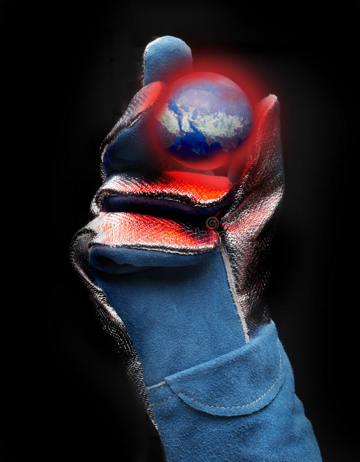 Global warming in the Middle East. Asbestos gloved hand holds red hot model of earth with view of the Middle East royalty free stock images