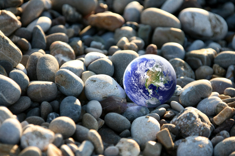 Global warning. Little globe image from nasa layered and placed in pebble stones royalty free stock image