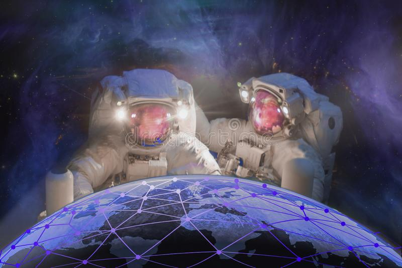 Global world telecommunication network connected around planet Earth. Two astronauts repait the planet Earth. Elements of this image furnished by NASA royalty free stock photos