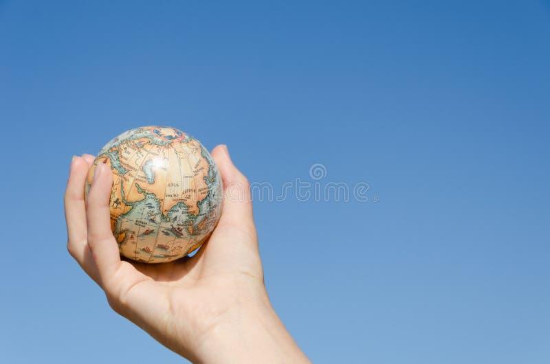Globale Erde in der Hand auf Hintergrund des blauen Himmels, Asien lizenzfreie stockbilder