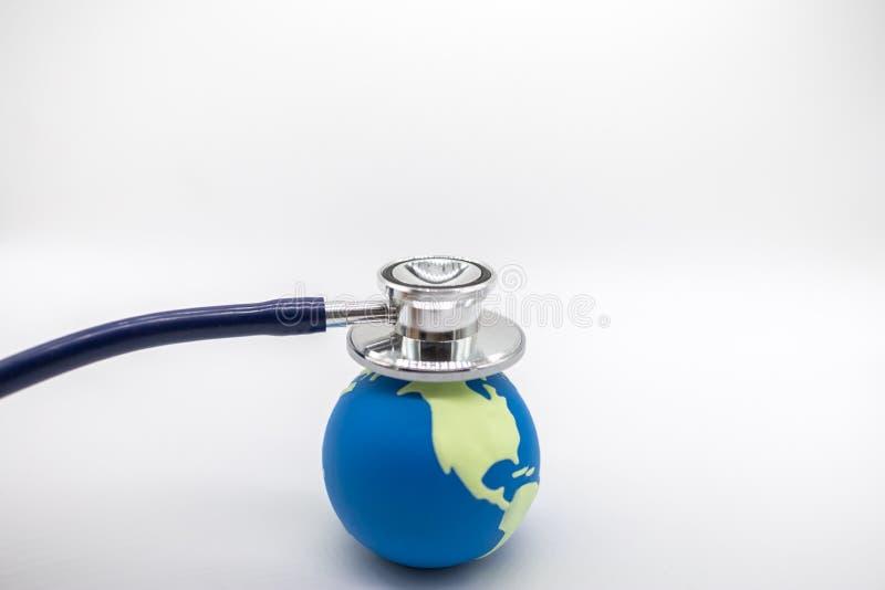 Globale Gezondheidszorg, Milieuecologie, Aardeconcept Sluit omhoog van arts Stethoscope op miniwereldbal op witte achtergrond en stock fotografie