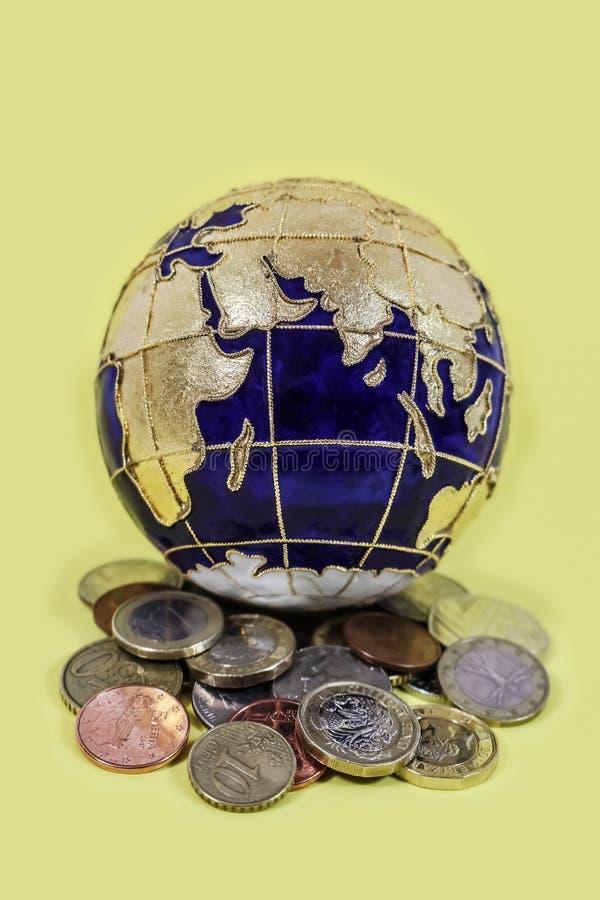 Globale Wirtschaft - schöne Emailweltkugel, die aus der ganzen Welt auf einem Stapel von Münzen auf gelbem Hintergrund sitzt - se lizenzfreies stockbild