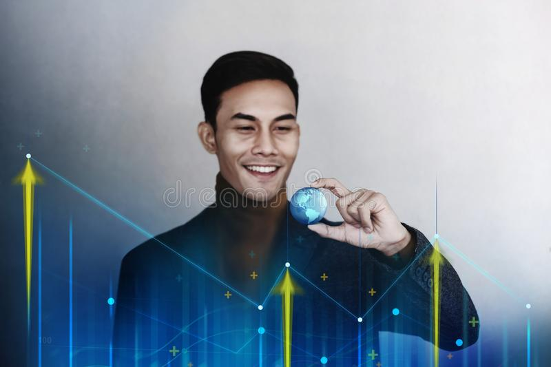 Globalização e conceito mundial do mercado do negócio Homem de negócios de sorriso feliz que guarda um globo azul transparente do fotos de stock