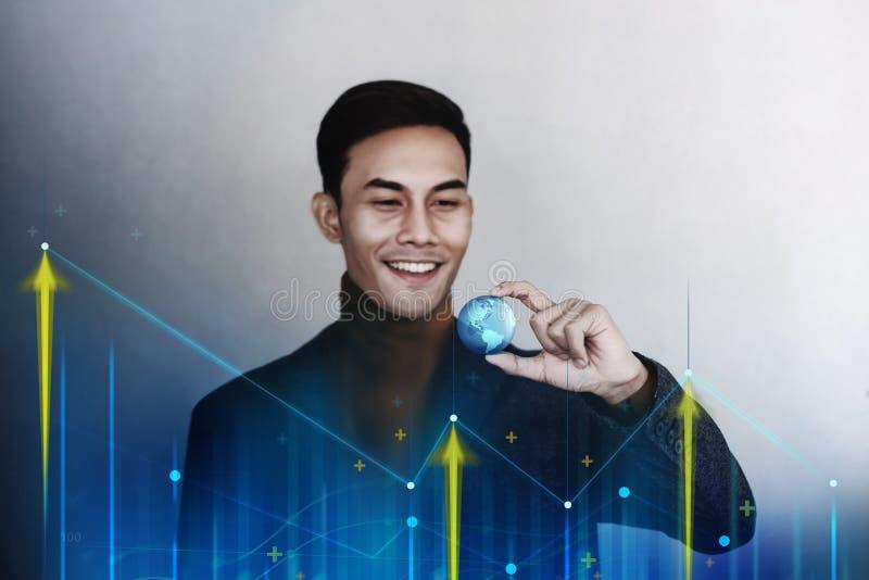 Globalización y concepto mundial del márketing de negocio Hombre de negocios sonriente feliz que sostiene un globo azul transpare fotos de archivo