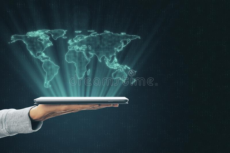 Globalization concept with digital world map layout above human hand with digital tablet. At abstract technology background stock images