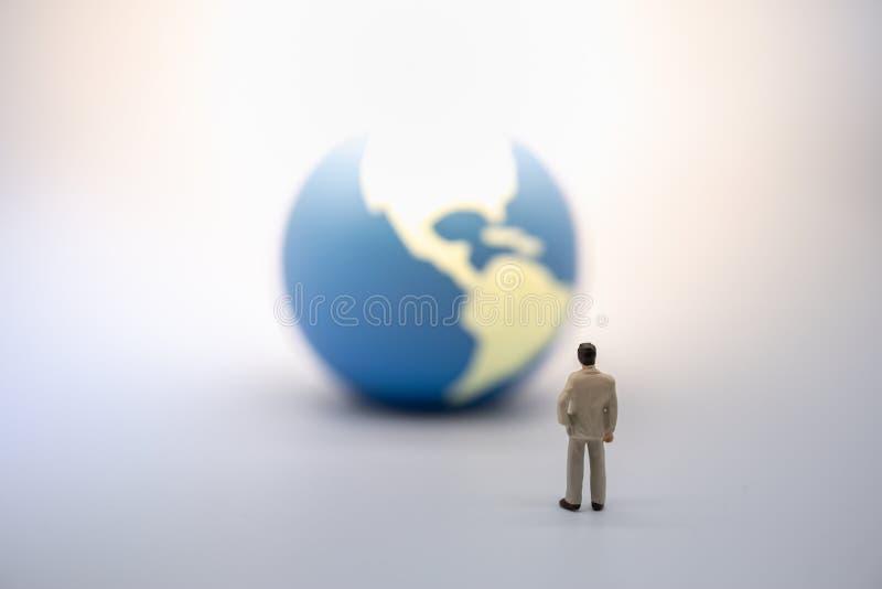 Globalny biznes i Planistyczny pojęcie Biznesmen miniatury postaci pozycja na zmielonym i patrzeć mini światowa piłka na bielu zdjęcie royalty free