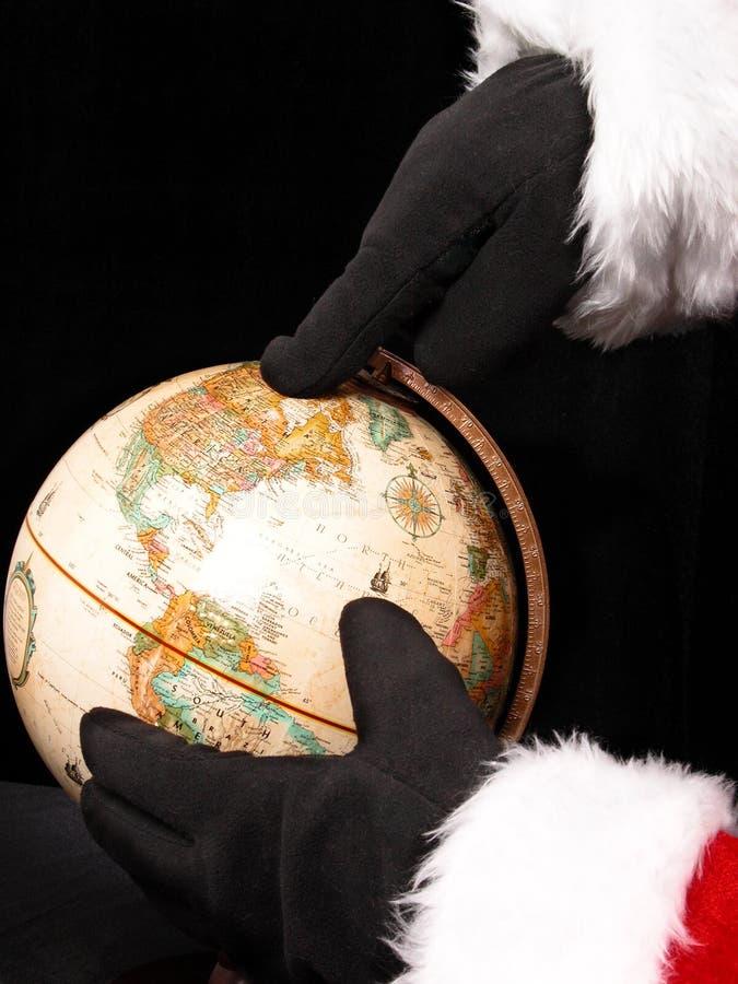 Globe avec des mains de Santa'a montrant le chemin image stock