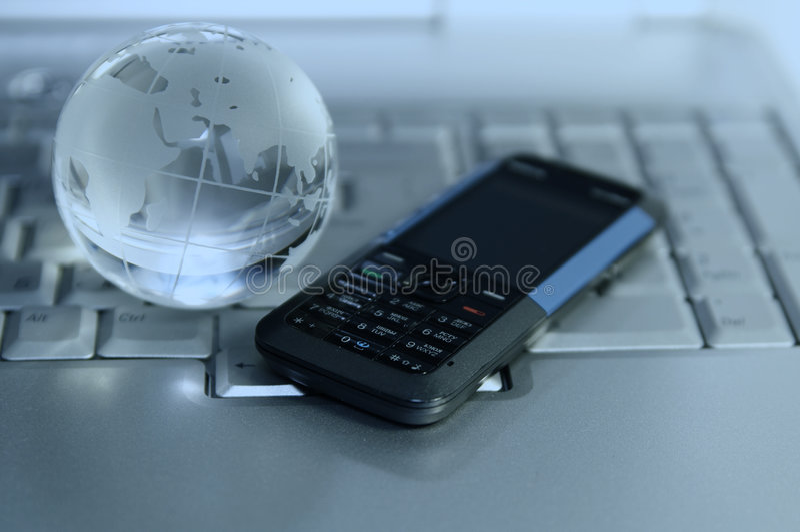 Globe cellulaire et en verre sur le clavier d'ordinateur portatif photo libre de droits