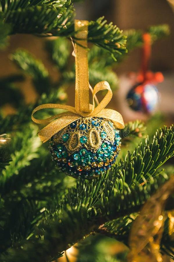 A jewel of the globe for Christmas tree. A globe for chistmans tree decoration, made of sequins, lace, vibrant colors: gold, turquoise, blue royalty free stock photography