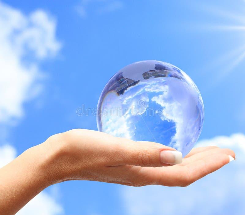 Globe dans la main humaine contre le ciel bleu. photographie stock