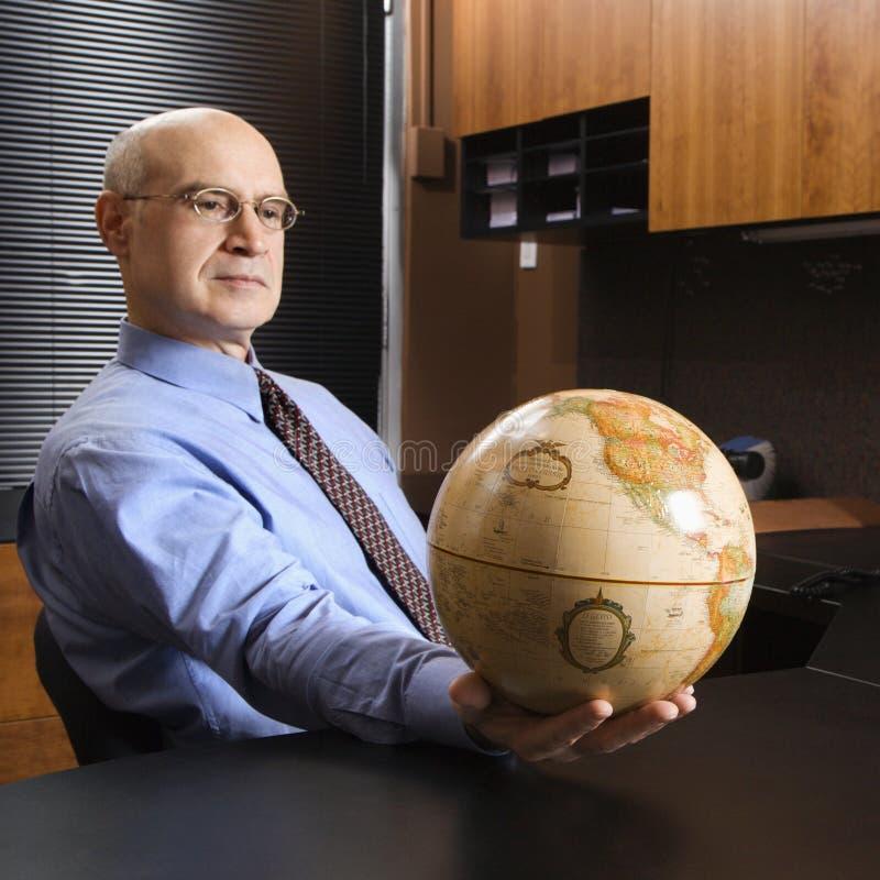 Globe de fixation d'homme d'affaires photographie stock libre de droits
