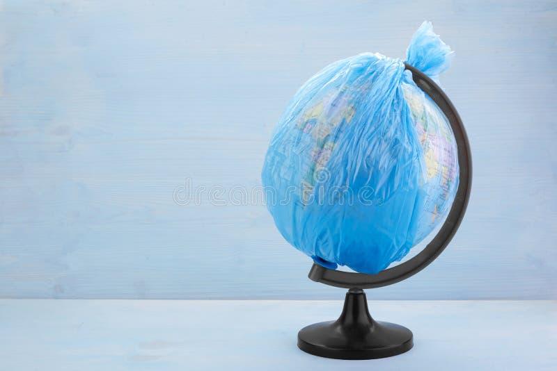 Globe de la terre de planète habillé dans un sachet en plastique de déchets sur le fond en bois bleu photos libres de droits