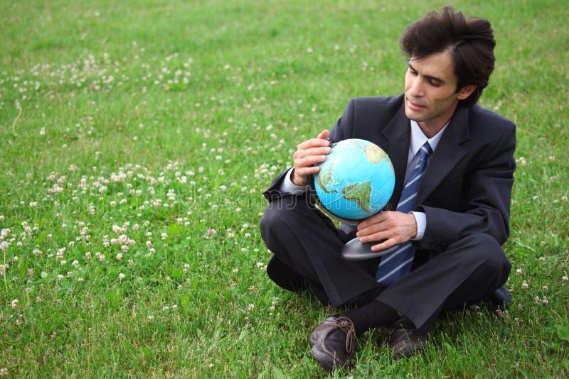 Globe de séance et de fixation d'homme d'affaires photographie stock libre de droits