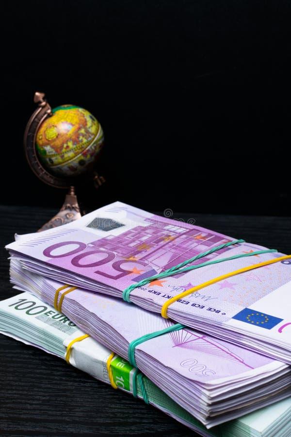Globe, earth map, Eu banknotes in denominations of hundred euros. Globe map sign over many euros bank notes ,international banknotes. globe royalty free stock photo