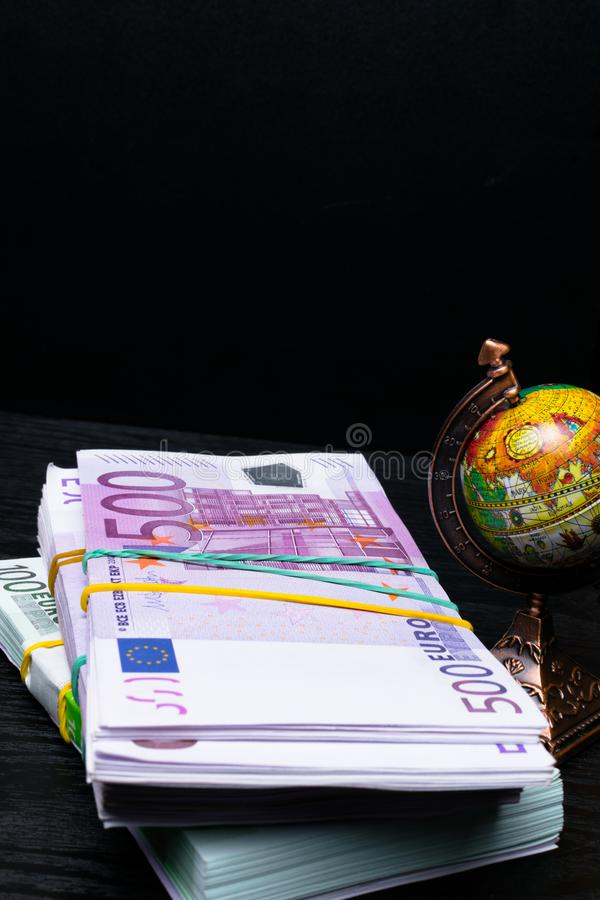 Globe, earth map, Eu banknotes in denominations of hundred euros. Globe map sign over many euros bank notes ,international banknotes. globe stock photos