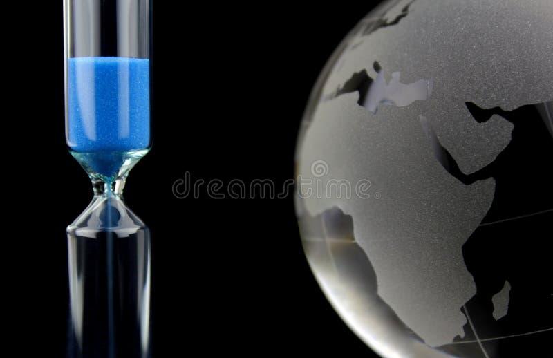 Globe en cristal et sablier bleu images stock