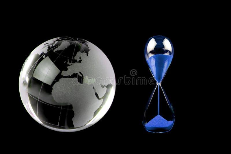 Globe en cristal et sablier bleu sur le fond noir photographie stock libre de droits