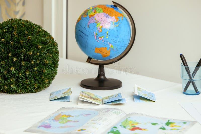 Globe et livres d'école sur la table photographie stock libre de droits