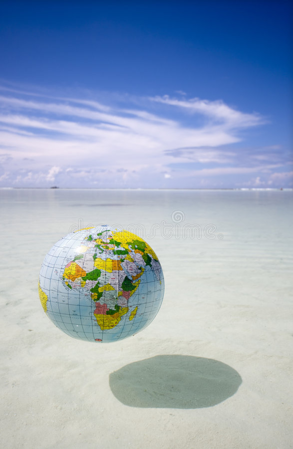 Globe Floating In Tropic Sea Royalty Free Stock Photos