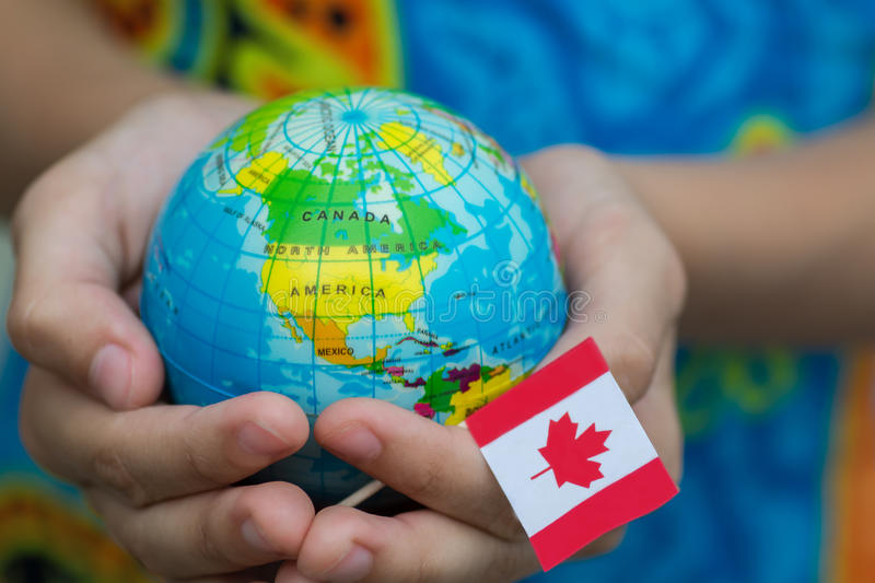 Globe in hand with the Canada flag. And map stock photography