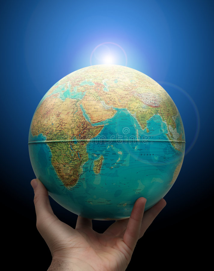 Globe in hand with rising sun. Planet earth holding in hand with rising sun behind. Success and power concept stock image