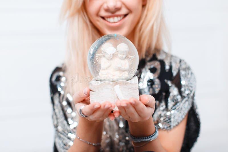 Globe magique de Noël de neige avec des anges dans des mains femelles photographie stock
