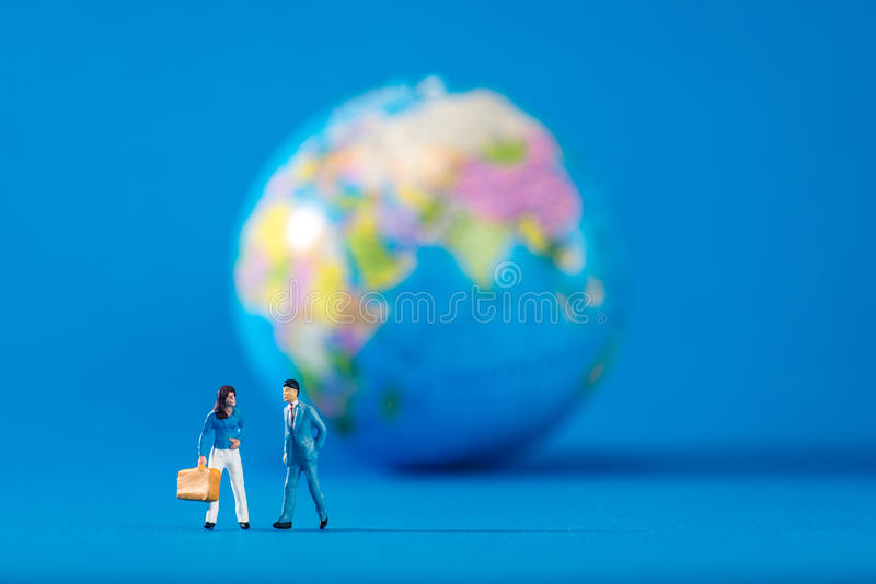 Globe and miniature people stock photography