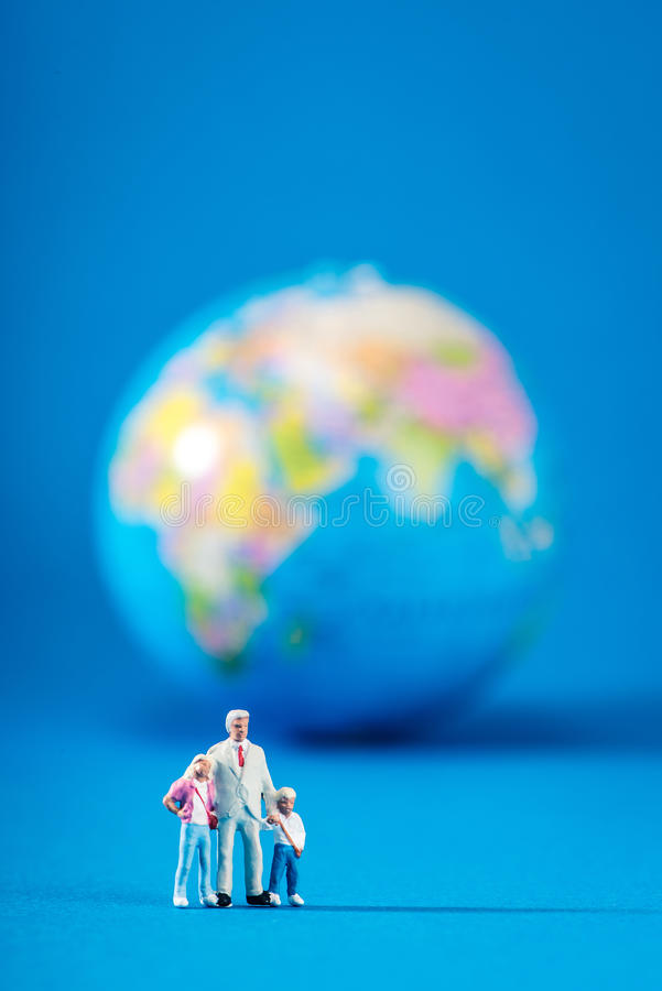Globe and miniature people royalty free stock photography
