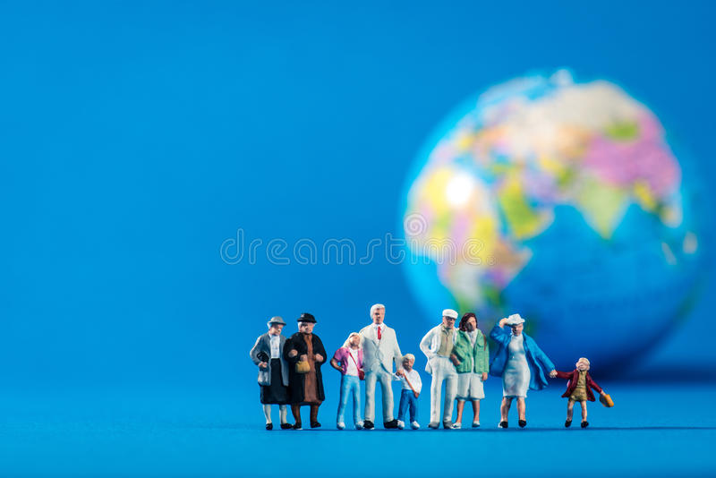Globe and miniature people stock photos