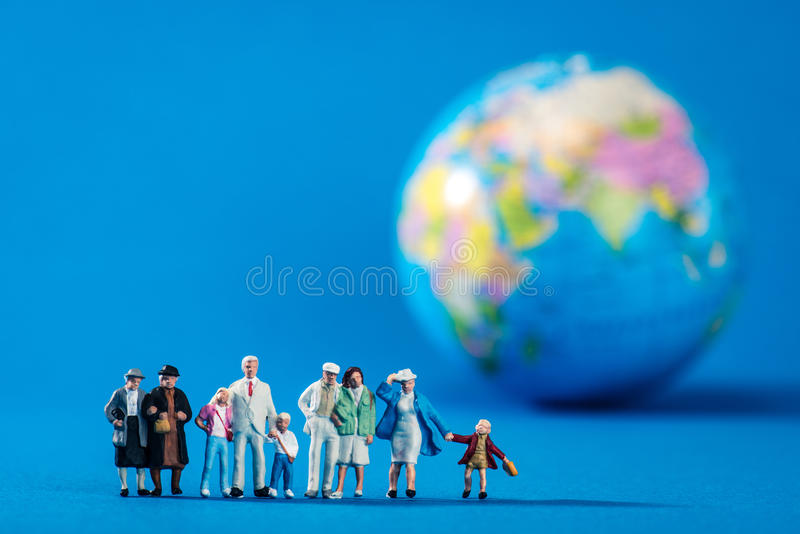 Globe and miniature people stock image