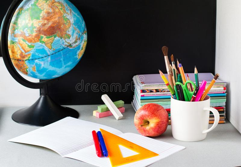 Globe, notebook stack and pencils on the table. Schoolchild and student studies accessories. Back to school concept royalty free stock images