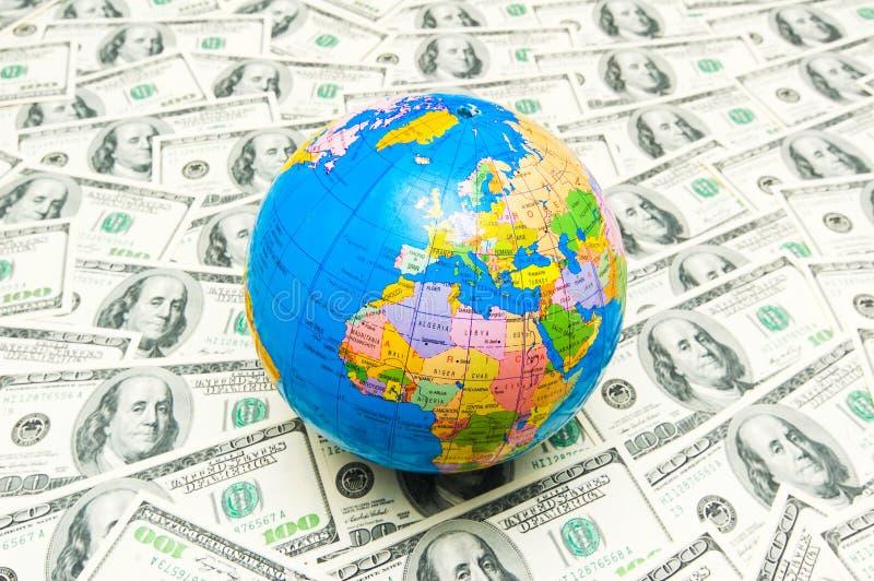 Globe over american dollar bank notes. Globe over many american dollar bank notes royalty free stock photo