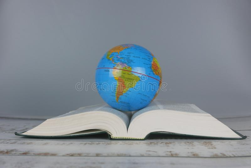 Globe over a book. world and education concept. Earth, global, planet, knowledge, geography, business, design, international, symbol, study, travel, learn, map stock images