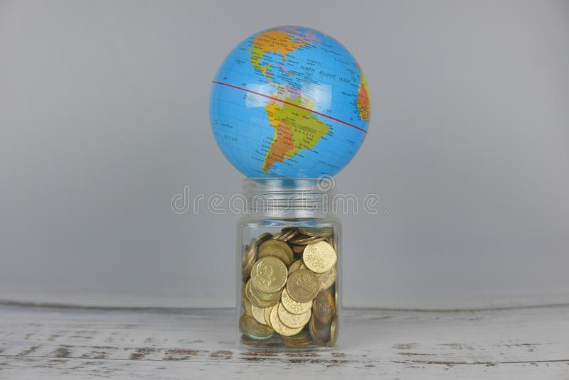 Globe over jar of coins. Money and world concept. Finance, business, global, data, network, exchange, communication, information, financial, map, earth royalty free stock photography