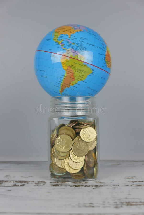 Globe over jar of coins. Money and world concept. Finance, business, global, data, network, exchange, communication, information, financial, map, earth stock image