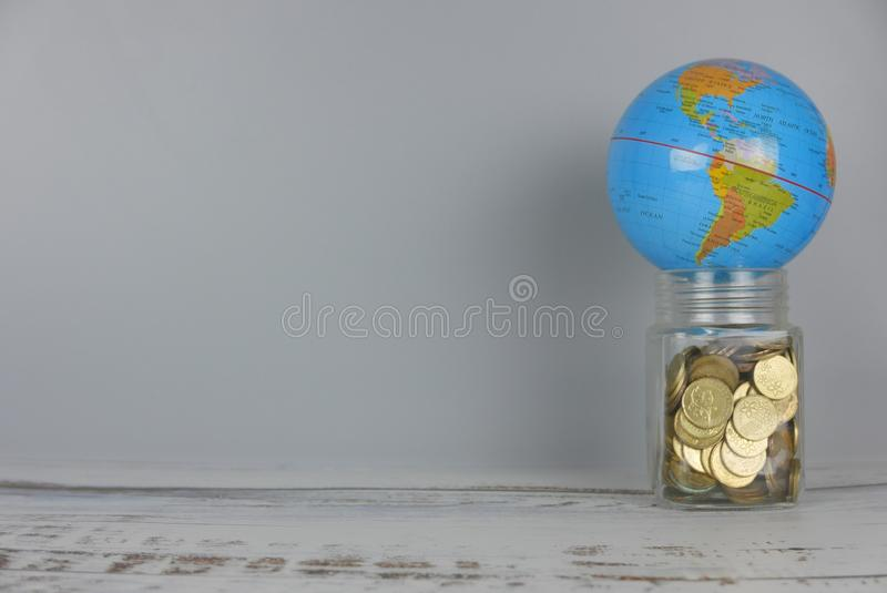 Globe over jar of coins. Money and world concept. Copy space for text and logo. Finance, business, global, data, network, exchange, communication, information royalty free stock photo