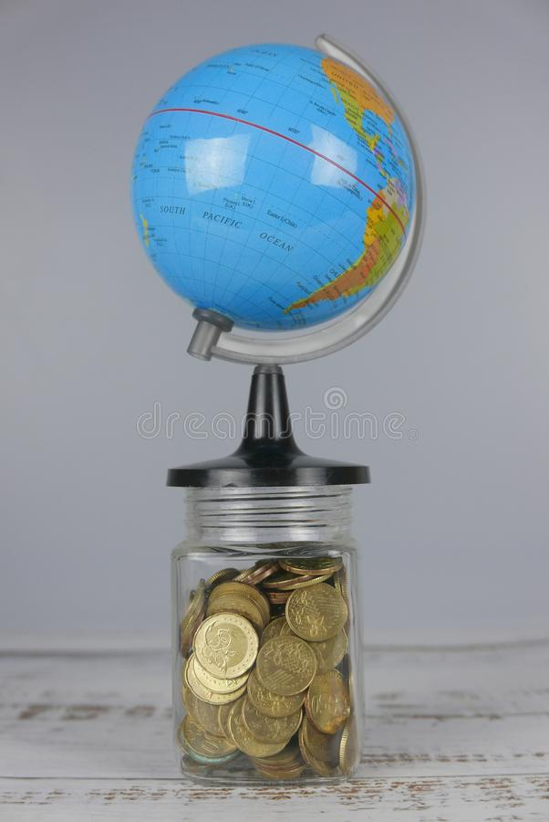 Globe over jar of gold coins. Money and world concept. Finance, business, global, data, network, exchange, communication, information, financial, map, earth royalty free stock photography