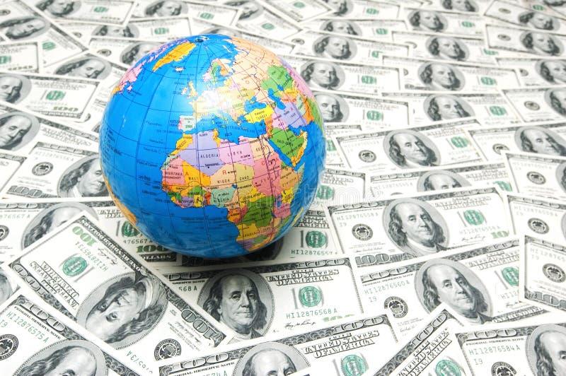 Globe over many dollar bank notes. Globe over many american dollar bank notes royalty free stock photography