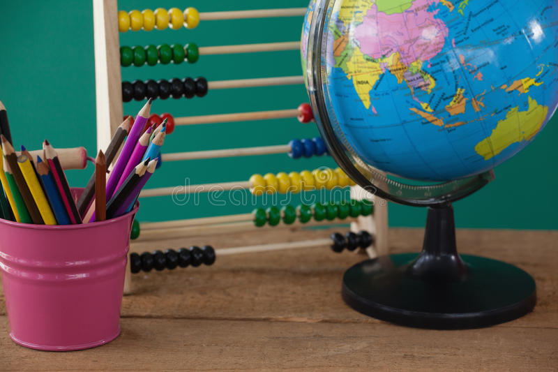 Globe, penholder and abacus on wooden table royalty free stock photo